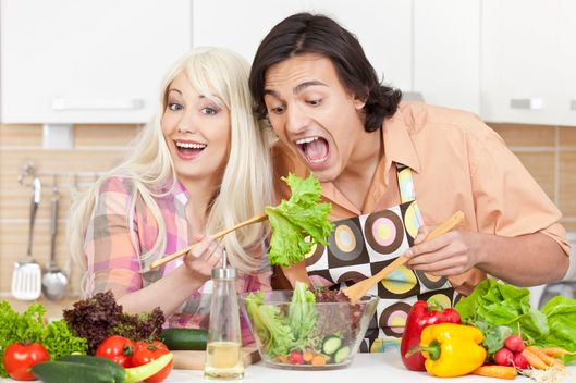 Smiling young couple with healthy lifestyle preparing fresh vegetable salad