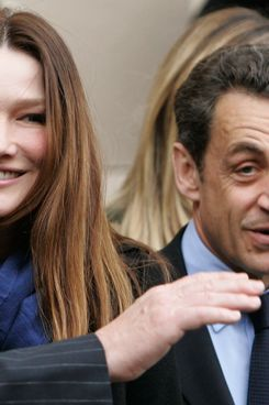Candidate for the 2012 French presidential election, Nicolas Sarkozy (R) and wife Carla Bruni-Sarkozy appear after voting at Lycee Jean De La Fontaine