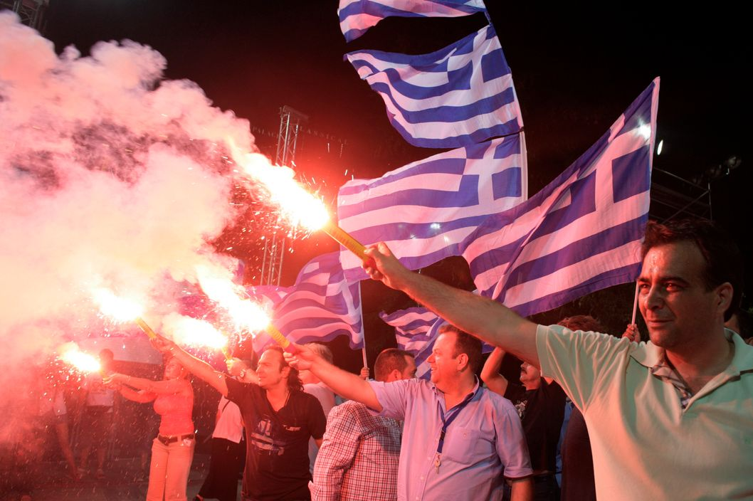 ATHENS, GREECE - JUNE 15:  Supporters of the 'New Democracy' political party light flares during a rally ahead of Sunday's general election on June 15, 2012 in Athens, Greece. The Greek electorate are due to go to the polls in a re-run of the general election on June 17, 2012 after no combination of political parties were able to form a coalition government. Recent opinion polls have placed the anti-bailout party 'Syriza' equal in popularity with the pro-bailout 'New Democracy' ahead of Sunday's general election which could determine whether Greece retains the Euro as its currency.(Photo by Milos Bicanski/Getty Images)