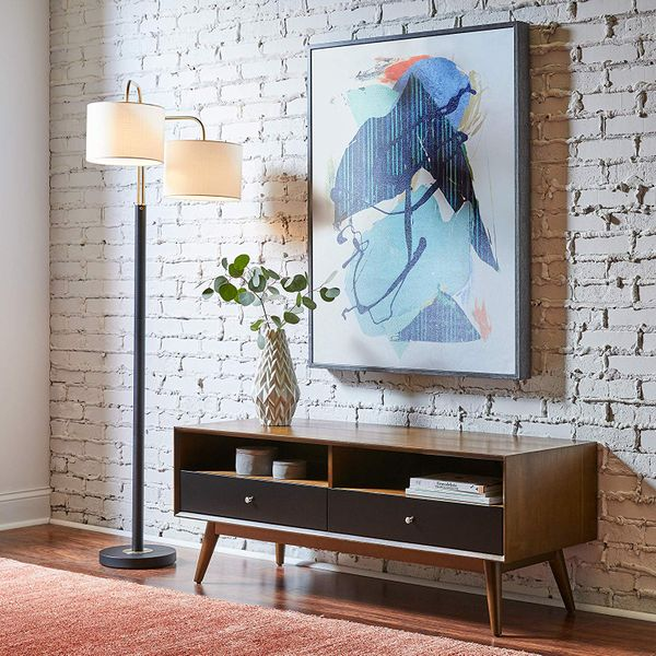 A black Wayfair floorlamp with a brass top leading to two linen lampshaded lights next to a large abstract painting, a vase, and a credenza. The Strategist - Very Tasteful Lamps from Amazon's Rivet and Stone and Beam Are on Sale