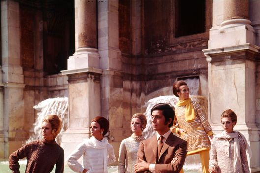 The Italian stylist Valentino posing among his models nearby Trevi Fountain. Rome, July 1967