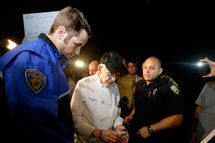 Homeless advocate Arnold Abbott, 90, of the nonprofit group Love Thy Neighbor Inc., center, gets his drivers license to hand to a  Fort Lauderdale police officer, Wednesday, Nov. 5, 2014, in Fort Lauderdale, Fla. Abbott and a group of volunteers were feeding the homeless in a public parking lot next to the beach when he was issued a summons to appear in court for violating an ordinance that limits where charitable groups can feed the homeless on public property.  Abbott w also recently arrested along with two pastors for feeding the homeless in a Fort Lauderdale park. (AP Photo/Lynne Sladky)