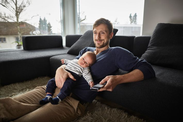 Father and baby boy in living room watching TV