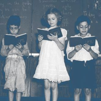 1930s line-up of 5 elementary school students in front of blackboard reading books with teacher looking on
