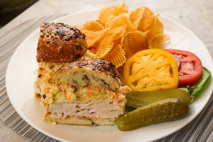 The Jewish Boy From Queens: roasted turkey on an onion pocket with sliced tomatoes, greens, Marilyn's coleslaw, and Russian dressing, with sliced pickles and onions.