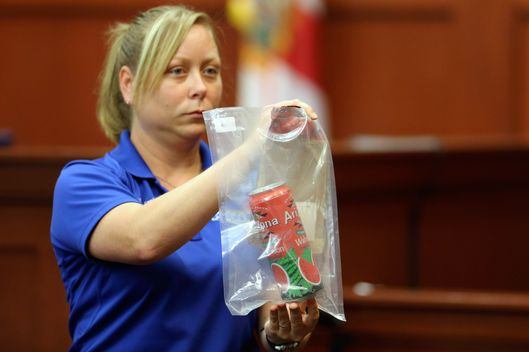 Diana Smith, crime scene technician for the Sanford Police Department, shows the jury a can of iced tea that was collected as evidence at the crime scene, during George Zimmerman's trial in Seminole circuit court June 25, 2013 in Sanford, Florida. Zimmerman is charged with second-degree murder for the February 2012 shooting death of 17-year-old Trayvon Martin.
