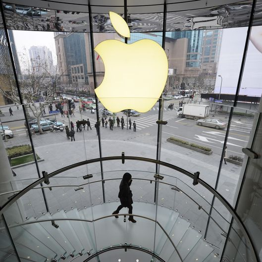 A customer walks under an Apple logo sign at an Apple shop in Shanghai on February 22, 2012. Despite suffering a setback in a Shanghai court on February 23, Proview Technology, a financially strapped Chinese company has reportedly opened up a US front in its legal war with Apple over the iPad trademark. AFP PHOTO / Peter PARKS (Photo credit should read PETER PARKS/AFP/Getty Images)
