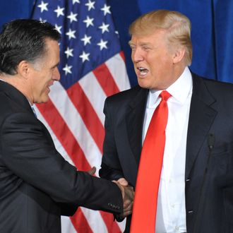 Businessman Donald Trump (R) shakes hands with Republican presidential hopeful Mitt Romney