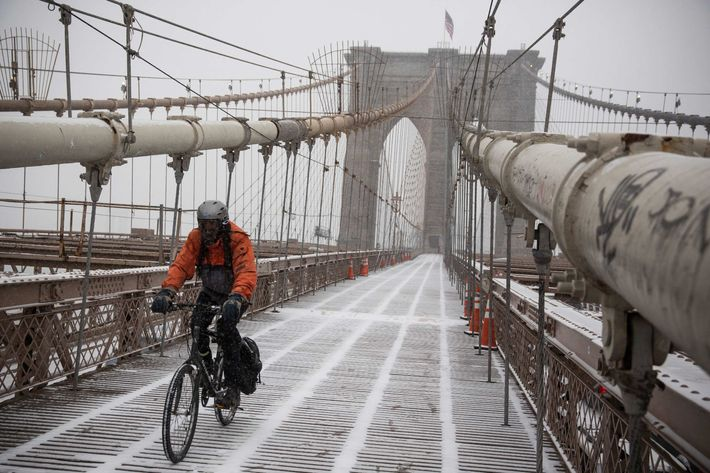 NEW YORK, NY - JANUARY 21:  A man rides his bike across the Brooklyn Bridge during a snow storm that is moving through the Northeast on January 21, 2014 in New York City. Along with dropping arctic tempertures the storm is expected to bring three to five inches by nightfall, with another four to six inches falling overnight.  (Photo by Andrew Burton/Getty Images)