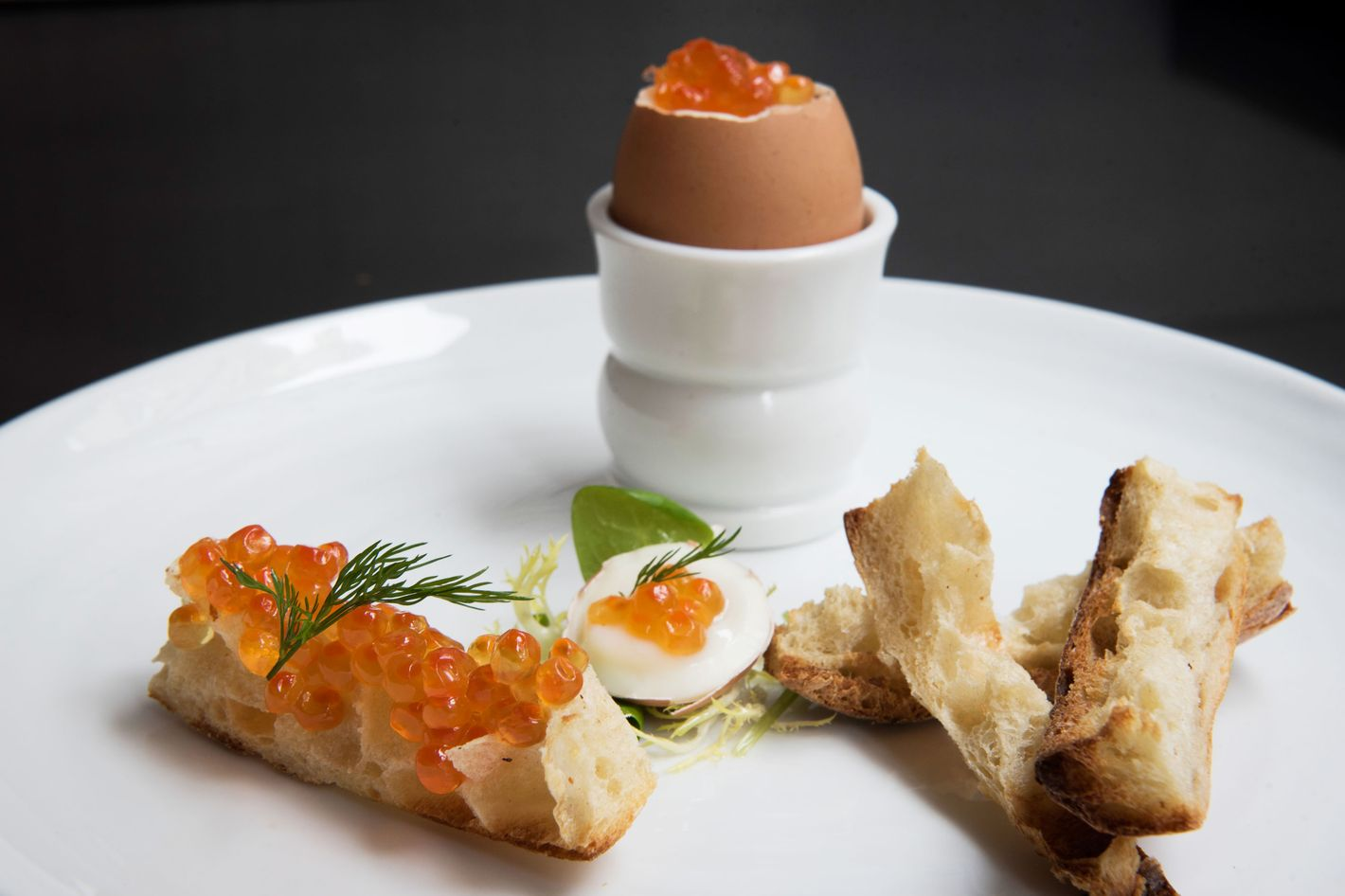 Soft-boiled eggs topped with salmon roe and dill, and served with butter soldiers for dipping.