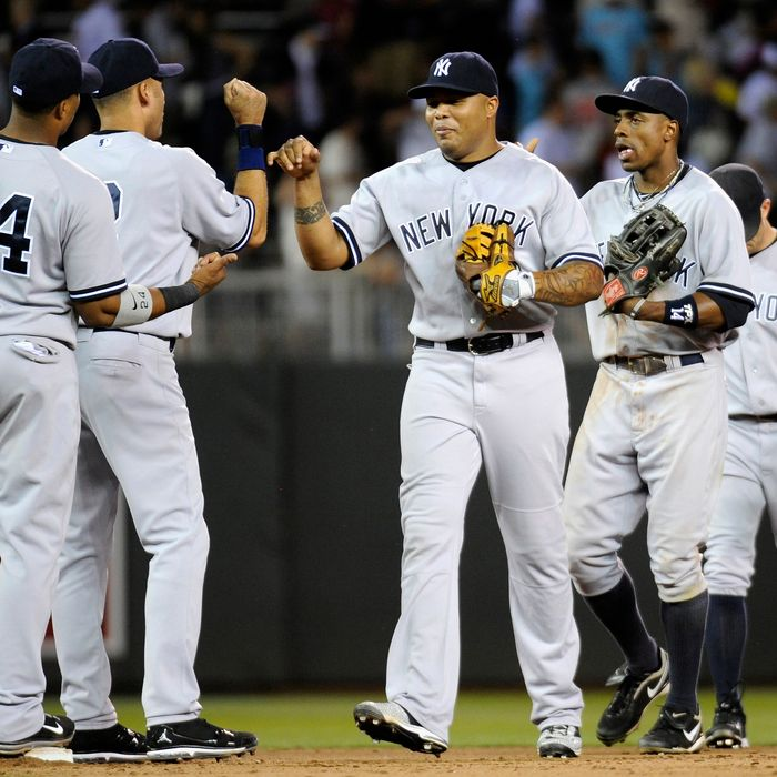 Robinson Cano #24, Derek Jeter #2, Andruw Jones #18, Curtis Granderson #14 and Brett Gardner #11 of the New York Yankees celebrate a win against the Minnesota Twins on August 18, 2011.