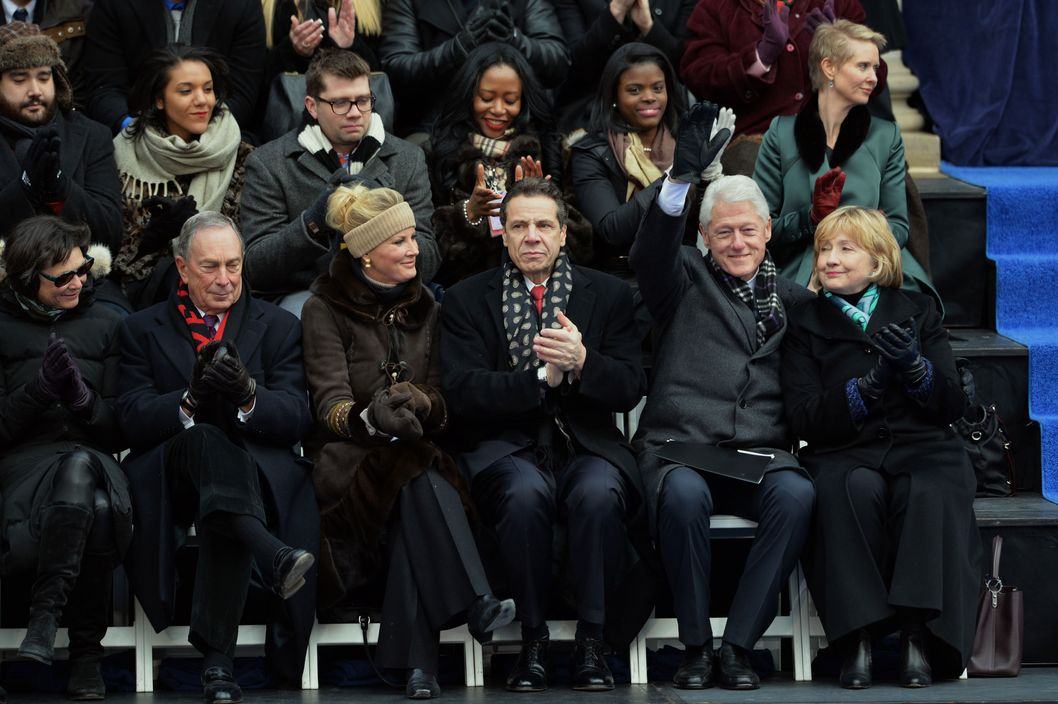 Former US President Bill Clinton (2nd R) waves with his wife Hillary Clinton at the inauguration of New York City Mayor Bill de Blasio on the steps of City Hall in Lower Manhattan January 1, 2014 in New York. Seated are New York State Governor Andrew Cuomo (C), his girlfriend cooking show host Sandra Lee, outgoing New York City Mayor Michael Bloomberg (2nd L) and his girlfriend Diana Taylor (L). AFP PHOTO/Stan HONDA        (Photo credit should read STAN HONDA/AFP/Getty Images)