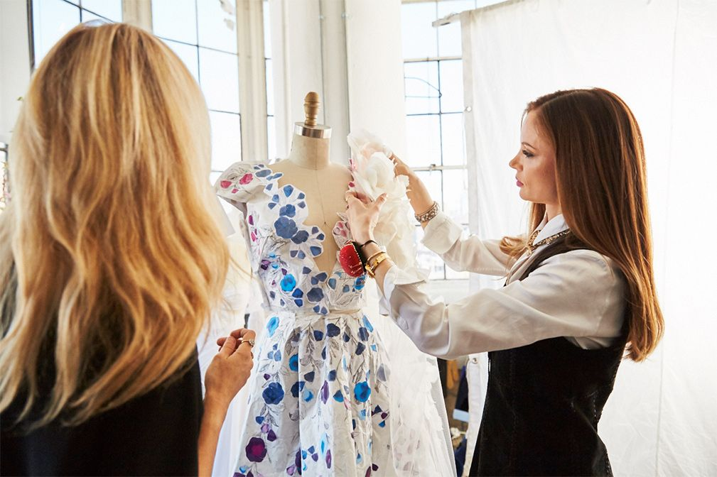 Marchesa tacking dress printouts onto a mannequin during the design stage