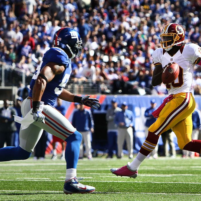 Quarterback Robert Griffin III #10 of the Washington Redskins avoids a tackle by outside linebacker Michael Boley #59 of the New York Giants during their game at MetLife Stadium on October 21, 2012 in East Rutherford, New Jersey.