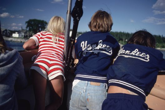 July 1981:  Two men in Yankees sports jackets and a girl in a red and white striped all-in-one hot pants suit reflect the colours of the American flag whilst boating in Maine.  (Photo by Ernst Haas/Ernst Haas/Getty Images)