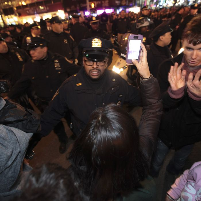 03 Dec 2014, New York City, New York State, USA --- New York, United States. 3rd December 2014 -- NYPD officers confront protestors in standoff near Rockefeller Center after thousands took to the streets to protest a Staten Island grand jury's failure to indict NYPD officer Daniel Pantaleo in the chokehold death of Eric Garner. -- Thousands of activists gathered throughout New York City after it was announced that the Richmond County grand jury investigating the death of Eric Garner failed to indict NYPD officer Daniel Pantaleo for use of an illegal chokehold. Arrests ensued. --- Image by ? Andy Katz/Demotix/Corbis
