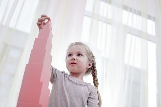 Young Girl Building a Tower with Pink Blocks