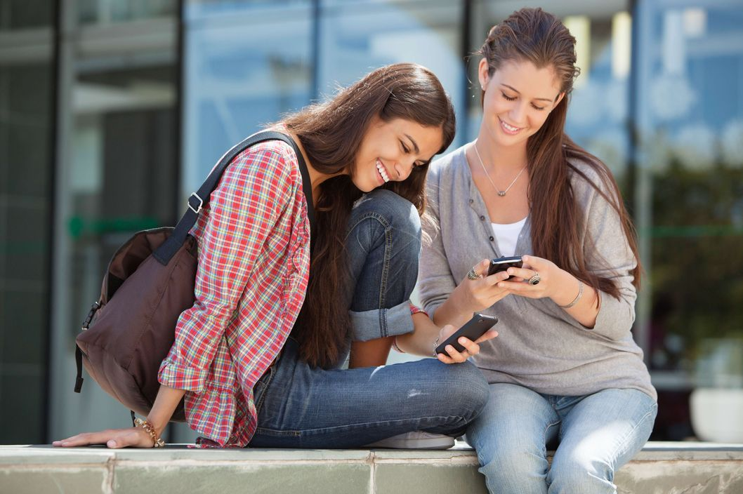 Young women using their mobile phones and smiling
