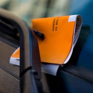 Orange parking ticket placed on windshield of car.