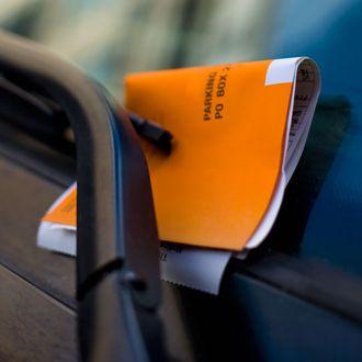Orange parking ticket placed on windshield of car.