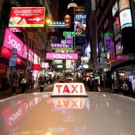 A photo taken on November 19, 2011 shows a taxi driving through the Central district of Hong Kong. As rush hour approaches the streets of Hong Kong, pedestrians can expect to bear witness to a familiar feeding frenzy as scores of shiny red scavengers compete for a sustenance of steady customers. With more than 18,000 taxis plying their trade to a population of over seven million, the night shift is a busy one. For taxi driver Alan Leung, the daily five-hour stint behind the wheel takes him from skyscrapers to street-corners as he traverses the tightly-packed territory in his bright red taxi. AFP PHOTO / ED JONES (Photo credit should read Ed Jones/AFP/Getty Images)
