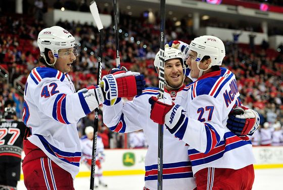 RALEIGH, NC - DECEMBER 01:  Artem Anisimov #42, Brandon Prust #8 and Ryan McDonagh #27 of the New York Rangers celebrate McDonagh's goal against the Carolina Hurricanes during play at the RBC Center on December 1, 2011 in Raleigh, North Carolina.  (Photo by Grant Halverson/Getty Images)