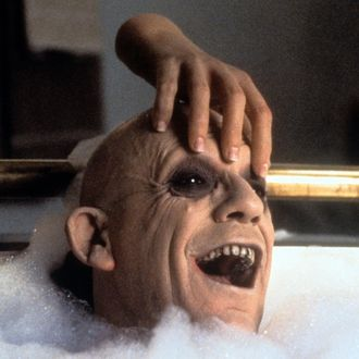 The Thing rubbing Christopher Lloyd's head in the bathtub in a scene from the film 'Addams Family Values', 1993.