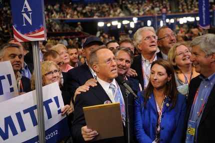 Scott Romney, brother of Republican presidential candidate Mitt Romney, center, announces Michigan's choice for presidential candidate while Ronna Romney McDaniel, committeewoman for the Michigan Republican Party, center right, listens at the Republican National Convention (RNC) in Tampa, Florida, U.S., on Tuesday, Aug. 28, 2012. Delegates are gathered in Tampa at the 40th Republican National Convention to select former Massachusetts governor Mitt Romney as their nominee for the next president of the United States.