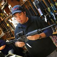 Jason Zielinski shows a customer an AR-15 style rifle at Freddie Bear Sports sporting goods store on December 17, 2012 in Tinley Park, Illinois.