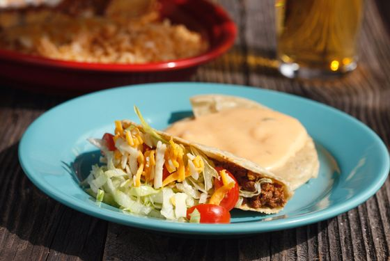 Part of El Original Combo #1: A picadillo beef crispy taco, one cheese enchilada with chili gravy, one beef tamale, a chile con queso tostada, guacamole, rice and beans.