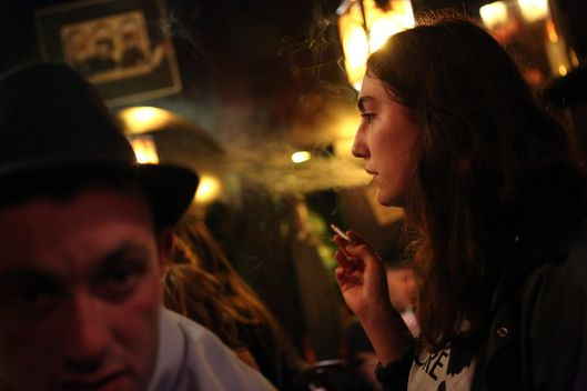 A woman smokes a cigarette at the Alt Berlin (Old Berlin) bar on April 22, 2014 in Berlin, Germany.