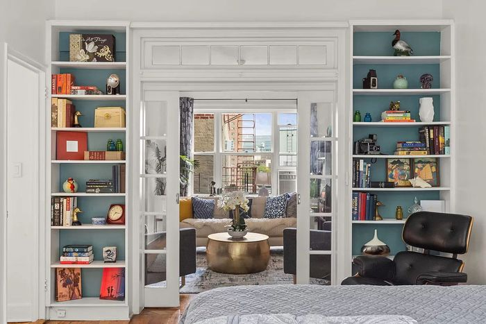 Living room with a bay window, fireplace, and built-in bookshelves.