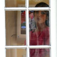 Jill Kelley looks out the window of her home as Gen. David H. Petraeus is seen on the television in the background on November 13, 2012 in Tampa, Florida. Kelley, who is reported to be involved with the military community at MacDill Air Force Base, reported receiving harassing emails to the FBI, which resulted in an investigation that revealed the sender to be Paula Broadwell, who was found to be having an affair with Gen. David H. Petraeus.