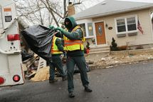 NEW YORK, NY - FEBRUARY 05:  Sanitation workers thrrow out debris from a flood damaged home in Oakwood Beach in Staten Island on February 5, 2013 in New York City. In a program proposed by New York Governor Andrew Cuomo, New York state could spend up to $400 million to buy out home owners whose properties were destroyed by Superstorm Sandy. The $50.5 billion disaster relief package, which was passed by Congress last month, would be used to fund the program. If the program is adopted, homeowners would be relocated and their land would be left as a natural barrier to help absorb future floods waters.  (Photo by Spencer Platt/Getty Images)