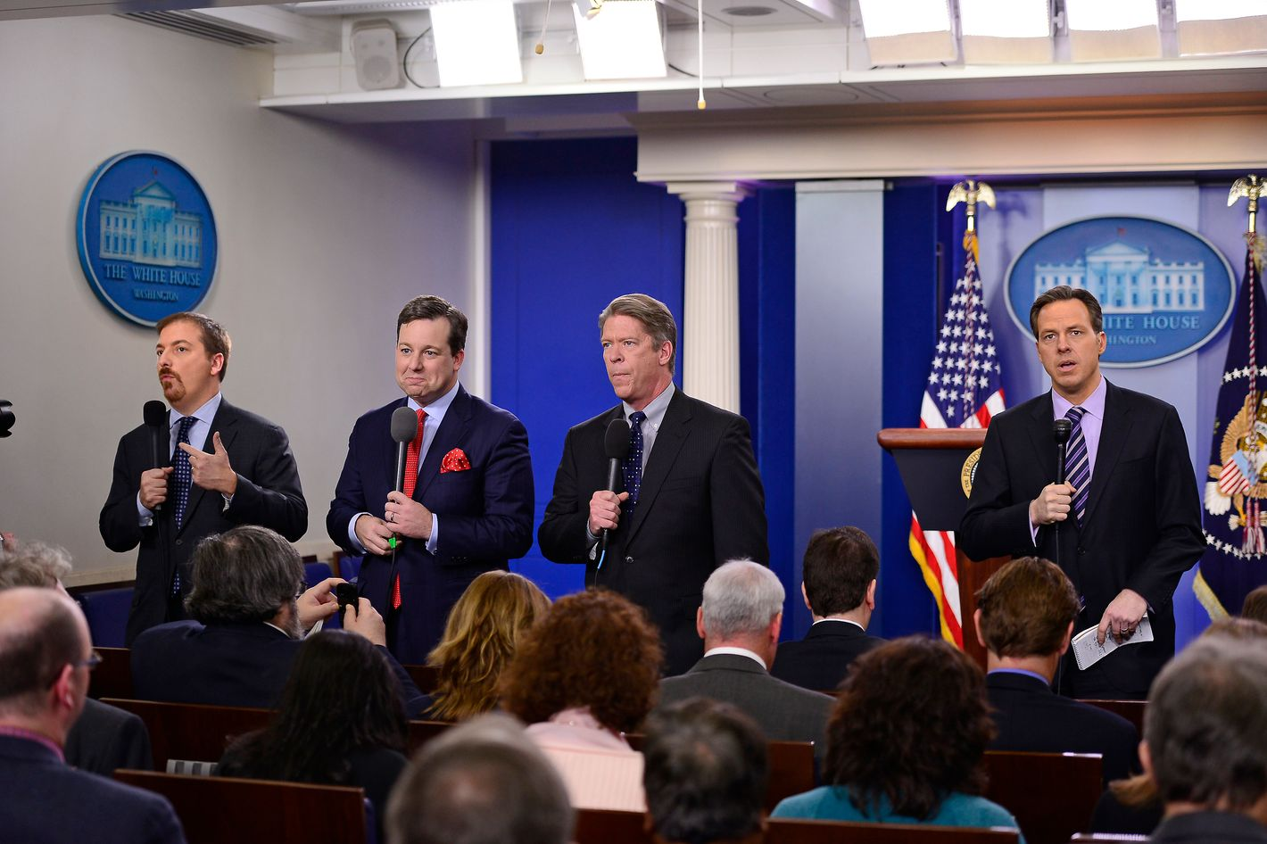 Chuck Todd of NBC News, left, Ed Henry of FOX News, second left, Major Garrett of CBS News, second right, and Jake Tapper of ABC News, right, do their stand-ups as they await the arrival of United States President Barack Obama, who will make a statement about how his administration will pursue a Weapons control policy in the wake of the Newtown tragedy in the Brady Press Briefing Room on Wednesday, December 19, 2012.  Vice President Joe Biden attended the announcement.