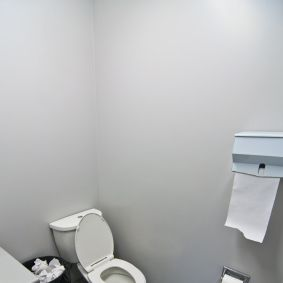 A toilet, sink and waste basket in an office washroom.