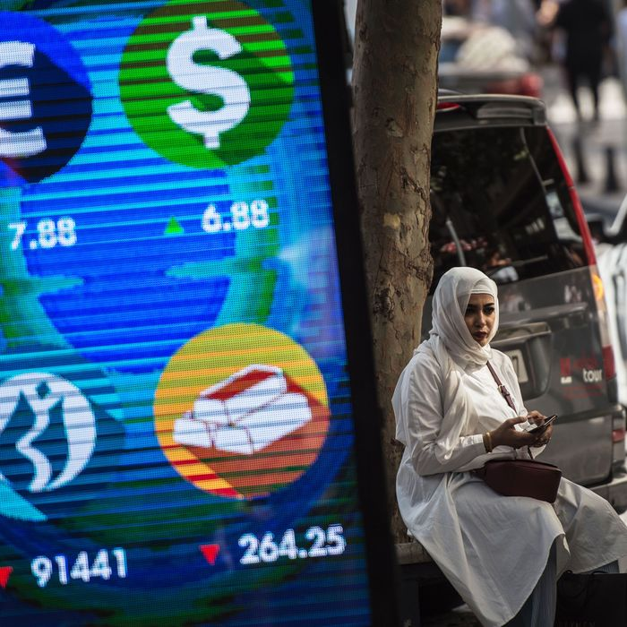 A woman sits beside a digital billboard giving updates on various currencies and the Turkish stock exchange in Istanbul.