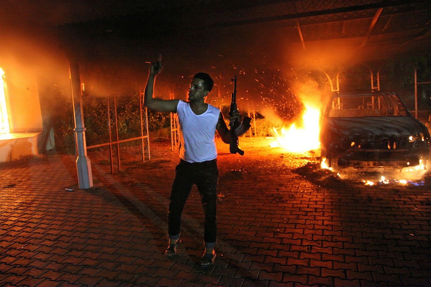 An armed man waves his rifle as buildings and cars are engulfed in flames after being set on fire inside the US consulate compound in Benghazi late on September 11, 2012. An armed mob protesting over a film they said offended Islam, attacked the US consulate in Benghazi and set fire to the building, killing one American, witnesses and officials said.