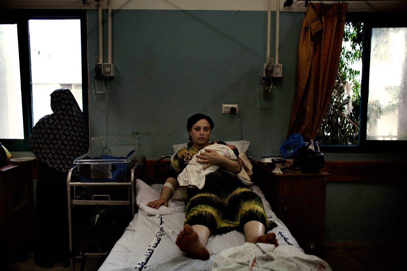 Maysa rests in a hospital bed after having given birth to a son, her 4th child. She lives in the Shatha camp and will go back home soon although numerous notifications from Israeli defense forces regarding homes that will be destroyed in airstrikes in the area makes her feel unsafe.