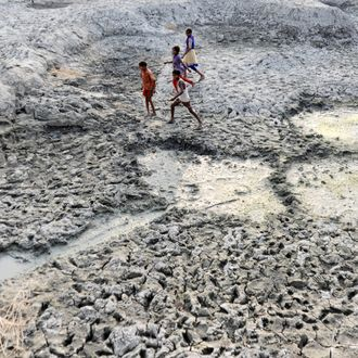 Children walk on the dry bed of parched mud that is the