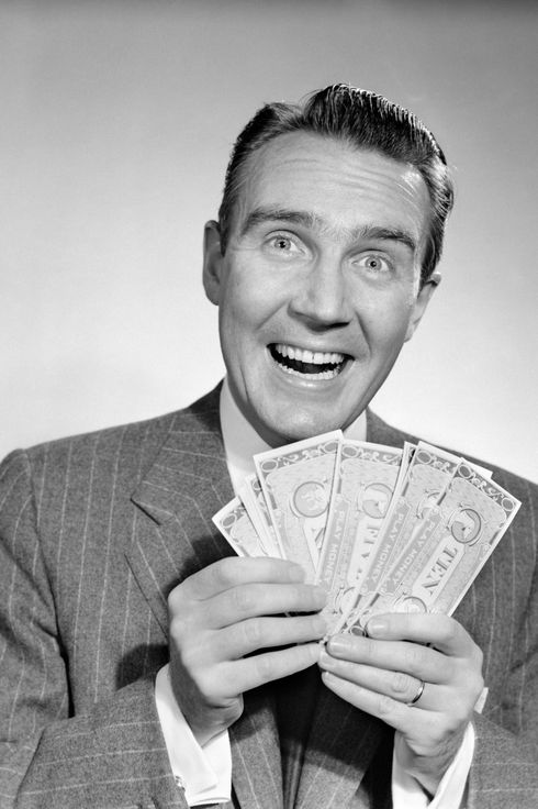 16 Feb 1959 --- 1950s happy man with exaggerated smile holding fan of money looking at camera --- Image by ? ClassicStock/Corbis