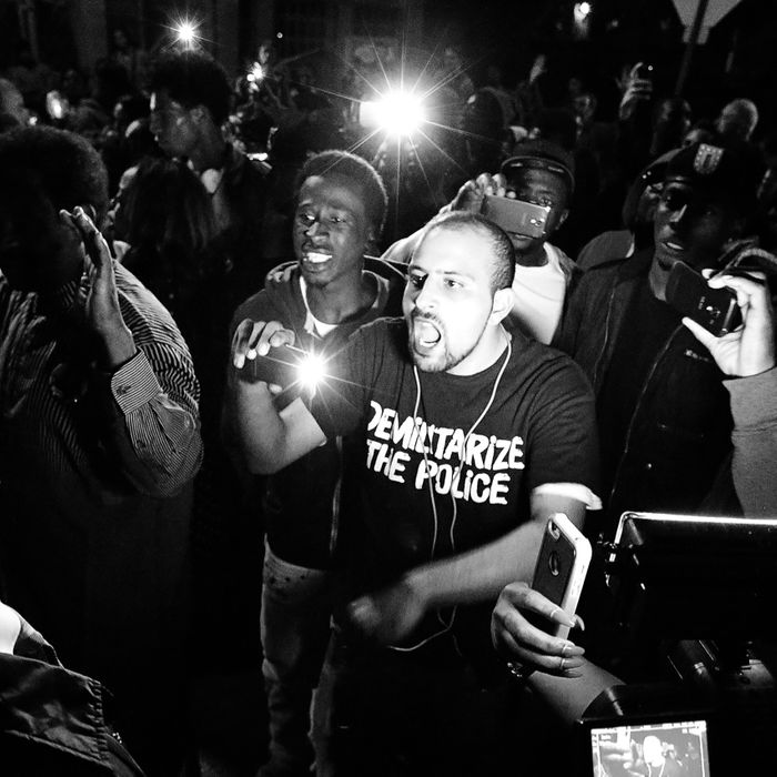Bassem Masri, center, confronting a St. Louis police officer in Ferguson, Missouri on Wednesday, Oct. 8, 2014.