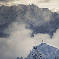 Lone climber standing on a snowy peak