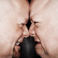Close up of Caucasian bald mid adult identical twin men standing face to face with angry expression.