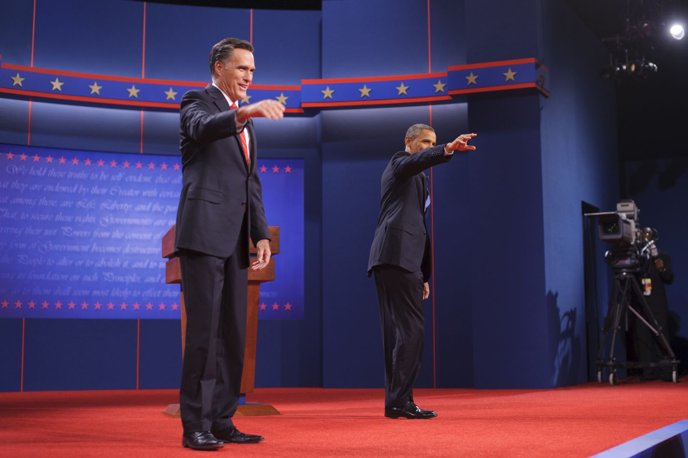 US President Barack Obama and Republican presidential candidate Mitt Romney wave October 3, 2012 after shaking hands as he arrives on stage for the first presidential debate at the University of Denver in Denver, Colorado.
