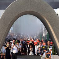 People offer prayers before a memorial monument during the 70th memorial service for the A-bomb victims at the Peace Memorial Park in Hiroshima on August 6, 2015.