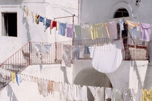 Monte Sant'Angelo, Italy --- Two boys walk under clotheslines strung across a piazza in Monte Sant Angelo. --- Image by ? Mimmo Jodice/Corbis