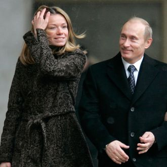 Russian President Vladimir Putin, center, and his wife Lyudmila, right, walk to a polling station in Moscow, Russia, Sunday, Dec. 2, 2007. Russians voted Sunday in a parliamentary election where the only question is whether President Vladimir Putin's party will win merely a strong majority of seats or a crushing share. A woman at left is unidentified. (AP Photo/Ivan Sekretarev)