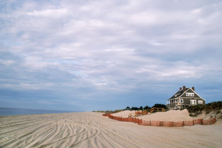 A grey shingle cottage sits on a dune overlooking a sandy beach in the Hamptons, Long Island, New York, September 1984. (Photo by Susan Wood/Getty Images)