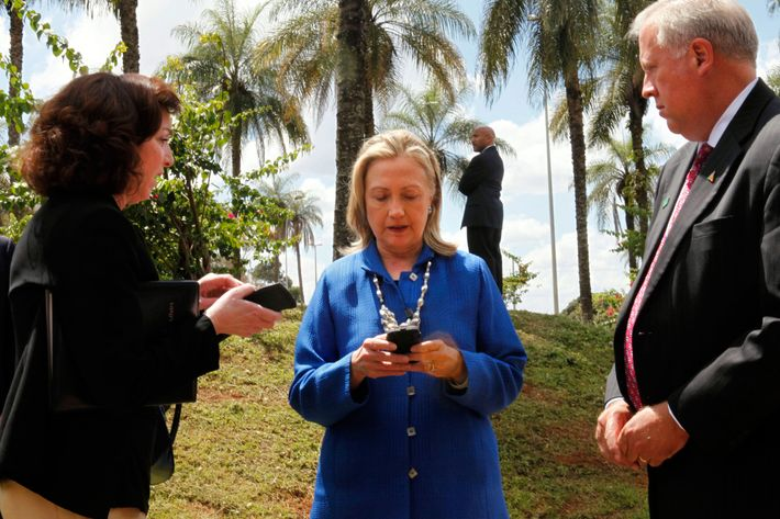 US Secretary of State Hillary Rodham Clinton (C) writes on her cell phone with Roberta S. Jacobson (L), US Assistant Secretary of State for Western Hemisphere Affairs, and US Ambassador to Brazil Thomas Shannon (R) in Brasilia, Brazil, before heading to Brussels on Tuesday April 17, 2012. AFP Photo / Pool / Jacquelyn MARTIN (Photo credit should read JACQUELYN MARTIN/AFP/Getty Images)